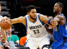 Minnesota Timberwolves' Karl-Anthony Towns, left, keeps the ball at arm's length from Dallas Mavericks' Harrison Barnes  during the second half of an NBA basketball game Monday, Jan. 9, 2017, in Minneapolis. The Timberwolves won 101-92. Towns and Barnes led their teams in scoring. (AP Photo/Jim Mone)